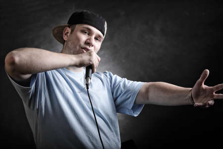 Rapper attitude rap singer hip Hop Dancer performing. Young man with microphone singing hand cool gesture black grunge background photo