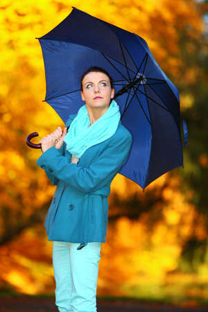 Fall lifestyle concept. Casual young woman girl walking with blue umbrella in autumnal park. Yellow gold colorful leaves background photo
