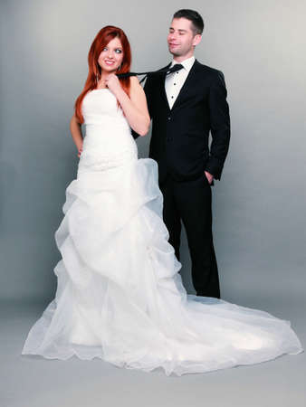 Wedding day. Portrait of happy married couple red haired bride and groom in full length. Woman pulling on mans tie, studio shot on gray background photo
