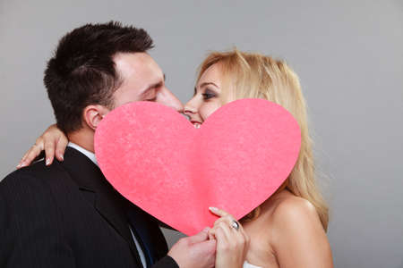 Wedding day. Happy blonde bride and groom kissing behind a red heart gray background photo