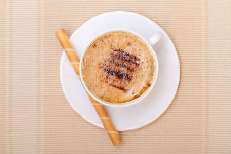 White cup of hot beverage drink coffee cappuccino latte with froth and sweet waffle roll stick with cream on brown . Studio shot. photo