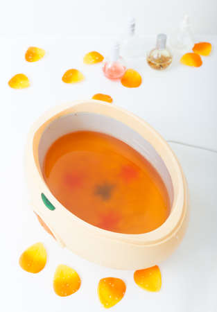 Orange parrafin wax in bowl and petals. Manicure and skincare in beauty spa salon. photo