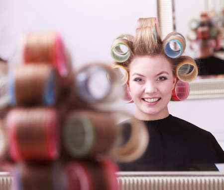 Portrait of happy woman in beauty salon. Cheerful blond girl with hair curlers rollers by hairdresser. Hairstyle. photo