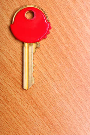 house coats: House key with red plastic coats caps on wooden table . Stock Photo