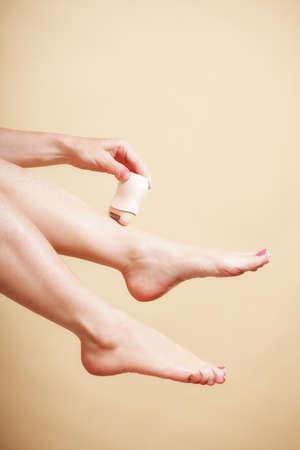 24368032 - Mujer que afeita sus piernas con la depilación máquina de afeitar  eléctrica en naranja. Belleza y concepto de cuidado de la piel del cuerpo. e14ab6262725