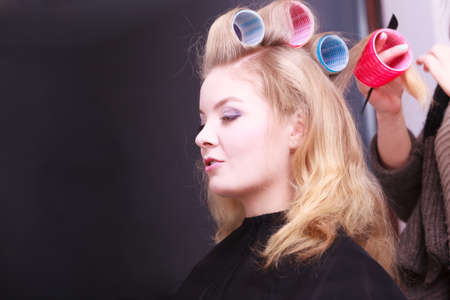 Beautiful young woman in beauty salon. Blond girl with hair curlers rollers by hairdresser. Hairstyle. photo
