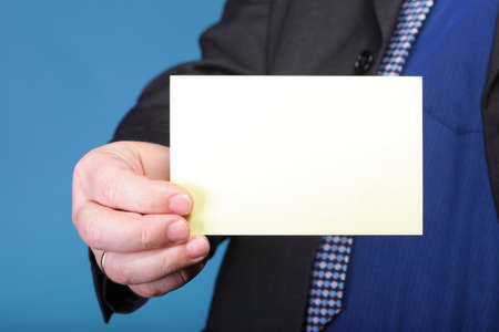 Closeup of blank business note card or signboard in man's hand blue background photo
