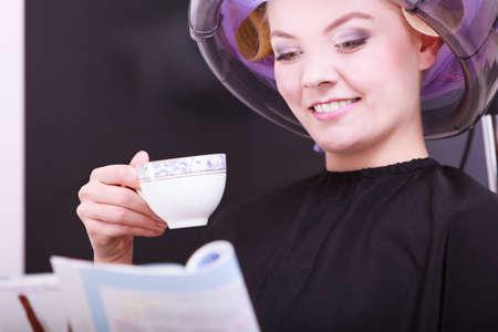 peluqueria: Mujer joven cliente femenina leyendo la revista y beber té café bebida caliente en salón de belleza peluquería. Chica en rodillos de cabello rizadores con secador de pelo se relaja por peluquero peluquería. Foto de archivo