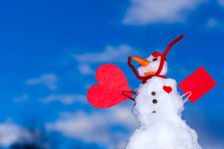 Little happy christmas snowman in red scarf and with clip heart love symbol valentine paper card text message outdoor. Winter season seasonal specific valentine's day. Blue sky background. photo