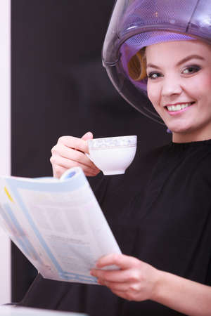 Young woman female client reading magazine and drinking hot beverage coffee tea in hairdressing beauty salon. Girl in hair rollers curlers with hairdryer dryer relaxing by hairdresser hairstylist. photo