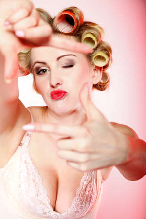Sexy woman preparing to party, girl in underwear curlers in hair having fun, making frame with hands, taking picture with imaginary camera pink background photo