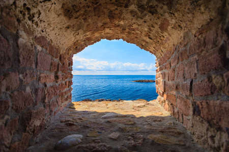 casing: View of blue sea and sky from hole in old stonewall wall. Seascape in stone window casing frame. Travel tourism. Stock Photo