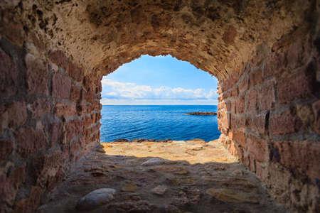 paysage marin: Vue sur la mer bleue et le ciel de trou dans vieux mur de Stonewall. Seascape dans le cadre de l'enveloppe de fen�tre en pierre. tourisme Voyage.