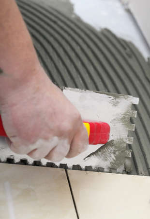 Home improvement, renovation - construction worker tiler is tiling, ceramic tile floor adhesive,  trowel with mortar Stock Photo - 24438078