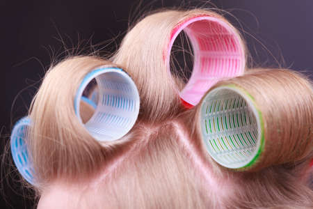Part of woman head. Blond girl with hair curlers rollers by hairdresser in hairdressing beauty salon. Hairstyle. photo