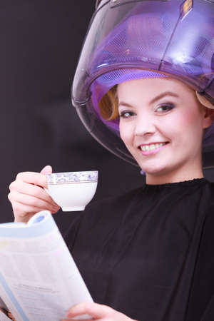 hot rollers: Young woman female client reading magazine and drinking hot beverage coffee tea in hairdressing beauty salon. Girl in hair rollers curlers with hairdryer dryer relaxing by hairdresser hairstylist.