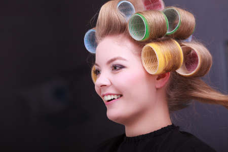 hair rollers: Beautiful young woman in beauty salon. Blond girl with hair curlers rollers by hairdresser. Hairstyle.
