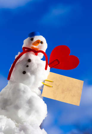 Little happy christmas snowman in blue screw top as hat red scarf and with clip red heart love symbol valentine paper card text message outdoor. Winter season seasonal specific valentine's day. Blue sky background. photo