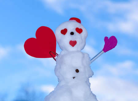 Little happy valentine snowman in red scarf and with clip heart paper card text message outdoor. Winter season seasonal specific valentines day. Blue sky background. photo