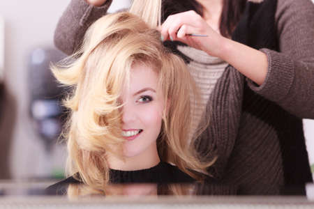 wavy hair: Beautiful smiling girl with blond wavy hair by hairdresser  Hairstylist with comb combing female client young woman in hairdressing beauty salon  Hairstyle  Stock Photo