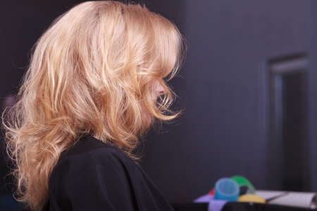 tratment: Female blond wavy hair. Back of woman girl head. By hairdresser in hairdressing beauty salon.