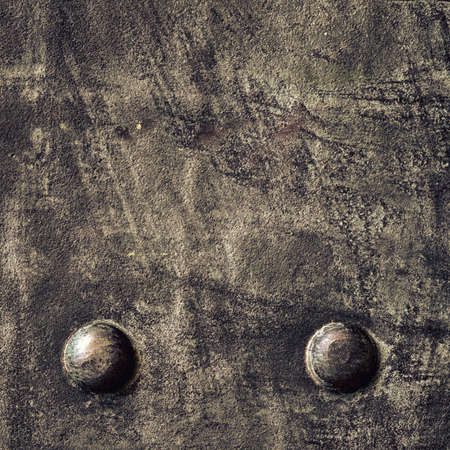 Closeup of grunge black metal plate with rivets and screws as background or texture. Square format. photo