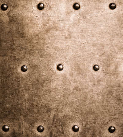 Closeup of grunge gold brown metal plate with rivets and screws as background or texture photo