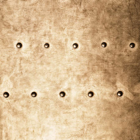 stell: Closeup of grunge gold brown metal plate with rivets and screws as background or texture. Square format.