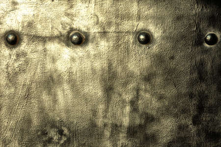 Closeup of grunge gray grey metal plate with rivets and screws as background or texture photo