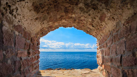 View of blue sea and sky from hole in old stonewall wall. Seascape in stone window casing frame. Travel tourism. photo