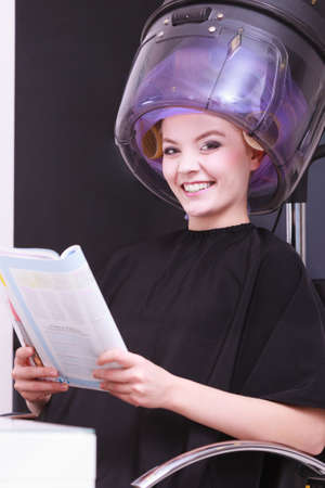 Young woman female client reading magazine in hairdressing beauty salon. Girl in hair rollers curlers with hairdryer dryer relaxing by hairdresser hairstylist. photo