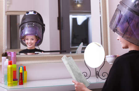 hot rollers: Young woman female client reading magazine and drinking hot beverage coffee tea in hairdressing beauty salon. Girl in hair rollers curlers with hairdryer dryer relaxing by hairdresser hairstylist. Mirror reflection. Stock Photo