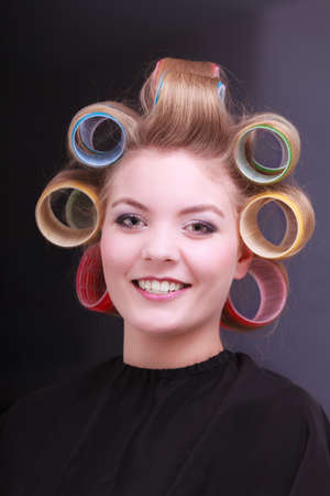 Portrait of happy smiling woman in beauty salon. Blond girl with hair curlers rollers by hairdresser. Hairstyle. photo