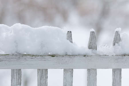 specific: Old white wooden wood fence covered with fresh snow on winter season. Seasonal specific. Stock Photo