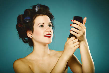 young woman preparing to party having fun, girl styling hair with curlers looking in the mirror  photo