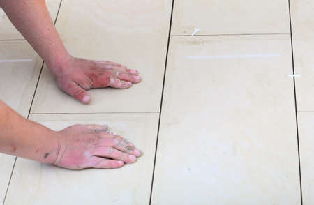 Home improvement, renovation - construction worker tiler is tiling, ceramic tile floor adhesive Stock Photo - 24567039