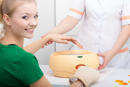 Happy woman in beauty spa salon with paraffin wax bowl  Skin body care