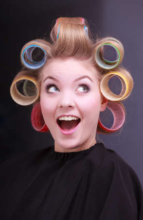 Portrait of funny happy woman in beauty salon  Cheerful blond girl with hair curlers rollers by hairdresser  Hairstyle   photo