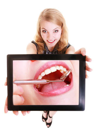 Happy blond girl showing ipad with photo of teeth and dental equipment photo