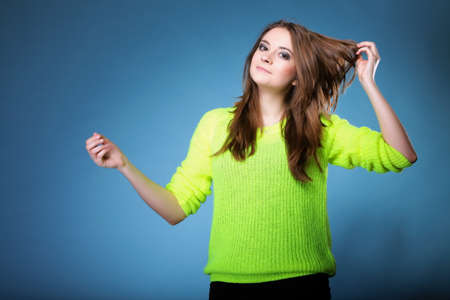 tenager: Portrait young woman wearing bright vivid colour sweater on blue background Stock Photo