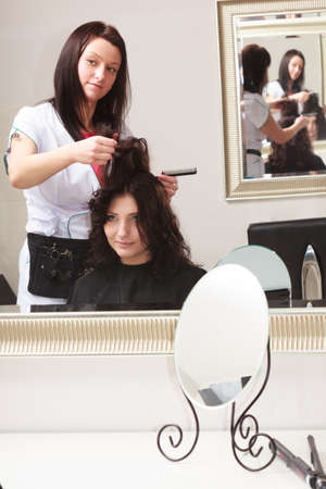 Curly brunette young woman looking at reflection of mirror by hairstylist. hairdresser combing female client. In hairdressing salon. photo