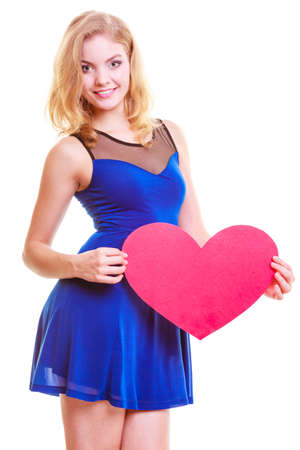 Red heart card. Love symbol. Portrait beautiful woman hold Valentine day symbol. Cute blonde girl in blue dress expressing tender feelings. Isolated studio shot photo