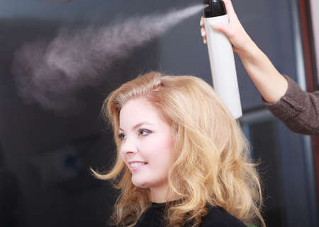 Girl with blond wavy hair by hairdresser  Hairstylist with hairspray and female client  Young woman in hairdressing beauty salon  Hairstyle  photo