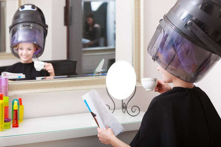 Young woman female client reading magazine in hairdressing beauty salon  photo