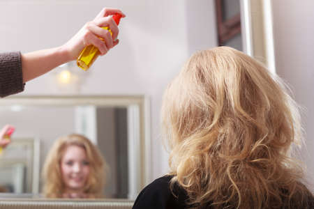 hairspray: Girl with blond wavy hair by hairdresser  Hairstylist with hairspray and female client  Young woman in hairdressing beauty salon  Hairstyle