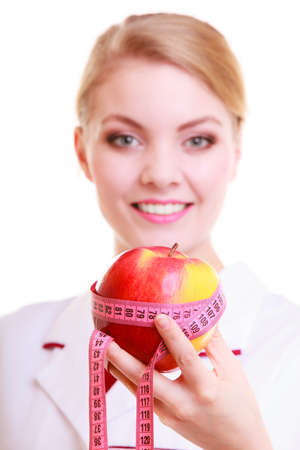 Woman in white lab coat recommending healthy food  Doctor dietitian holding fruit apple and measure tape photo