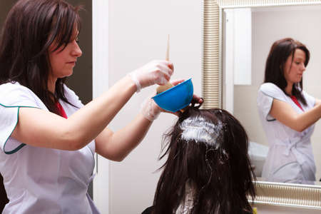 Professional female hairdresser applying color to female customer at design hair salon, woman having her hair dyed, Hair dye colouring in process  版權商用圖片