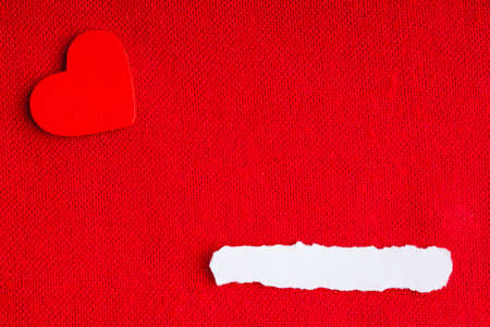 Piece scrap of white paper blank copy space and heart symbol of love on red fabric textile material background. Valentines day. photo