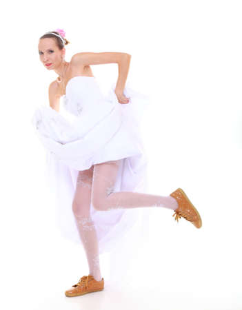 Wedding day. Running bride funny young woman wearing sporting shoes isolated on white photo
