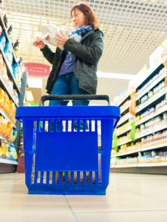 view of blue empty shopping basket and woman client at supermarket photo